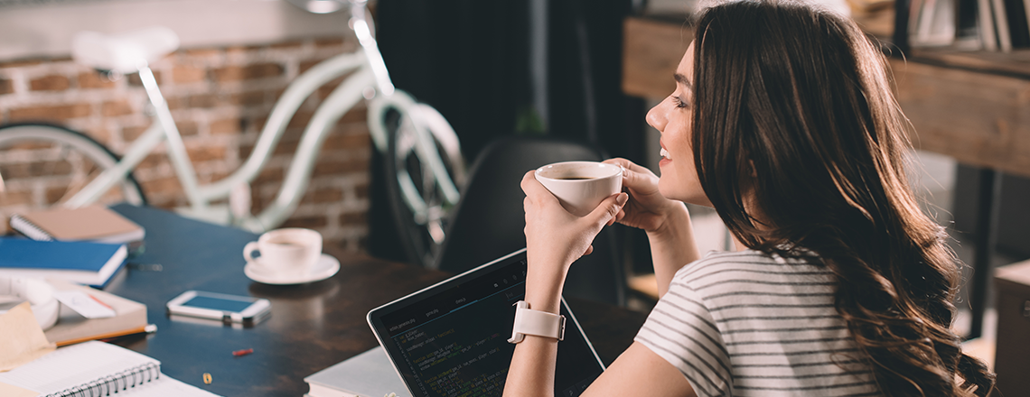 Girl sitting at desk with cup of coffee on computer